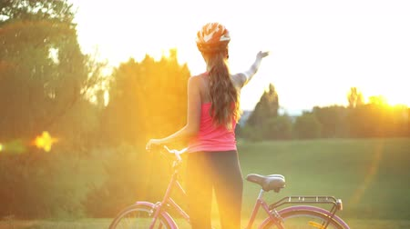 Girl in helmet on bicycle in summer park with city on horizon . Color tone on shiny sunlight background. Wideo