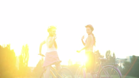 Children in helmet on bicycle go from hill on bicycle wave buy in summer park on horizon . Color tone on sun flare background.