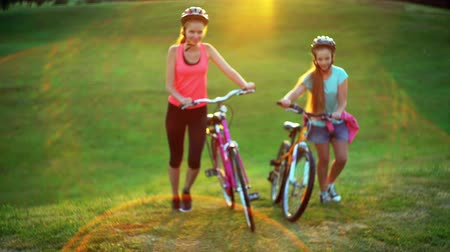 Children in bicycle helmet top hill by walk bike in summer park . Color tone on sundogs flare background and green grass.