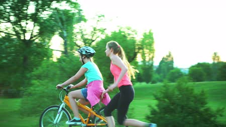 kendi : Children put on bicycle helmet and teach ride bike in summer park .Youngest girl is riding down the hill on her own, other is jumping joyfully, raising her arms up.