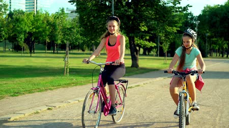 Children in helmet on bicycle by cycleway in summer park with tree on city background. Wideo