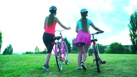 Kids in bicycle helmet top hill by walk bike in summer park aganist blue sky with clouds. Back view and low angle children feet wearing gumshoes. Wideo