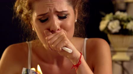 Girl cries and burns couple love photo memory in stress over burning candles on dark background.