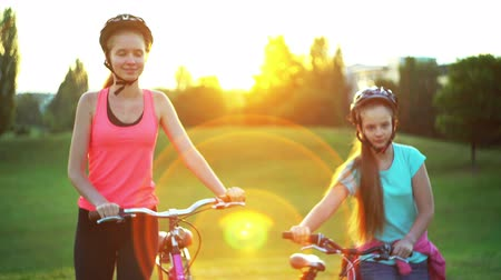 Children in bicycle helmet go on hill walk bike in summer park . Color tone on sundogs flare background.