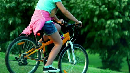 Child put on bicycle helmet teach ride bike in summer park . Girl is riding down hill on hight speed.