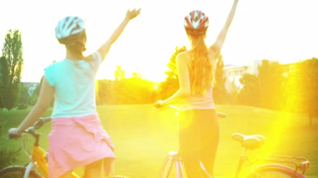 Children in helmet on bicycle rising sun salute in summer park on hillock with city on horizon . Color tone on shiny sunlight background.