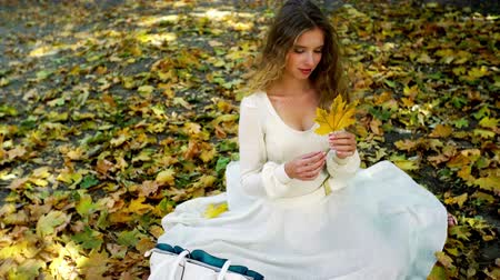 Autumn girl in fashion and lifestyle lyrics style. Beautiful woman with yellow leaf in hand sitting on fall land.