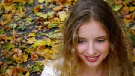 Face of girl and neckline playing by hair to and fro with autumn leaves in park background in fashion and lyrics style.