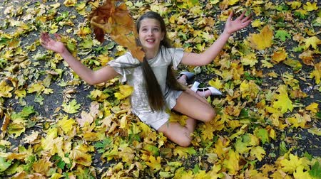 Autumn child girl in fashion and lifestyle lyrics style. Beautiful kid pick up bouquet of yellow leaves sitting on fall land and toss up. Wideo