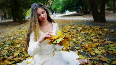 Autumn girl in fashion and lyrics style. Beautiful woman in white romantic lace dress play with bouquet of yellow leaves in hand walking park outdoor.