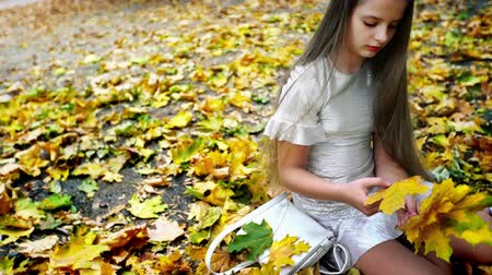 Autumn child girl in fashion and lifestyle lyrics style. Growing up of beautiful teenager pick up bouquet of yellow leaves sitting on fall land in park.
