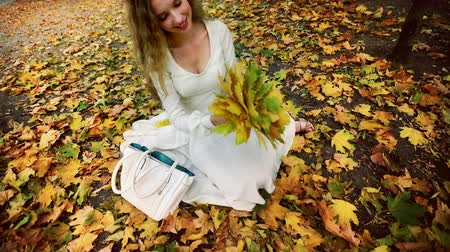 Autumn girl in fashion and lifestyle lyrics style. Beautiful woman pick up bouquet of yellow leaves in hand sitting on fall land and toss up.