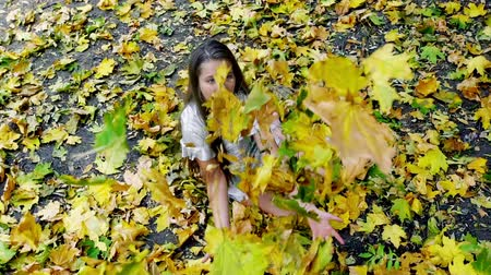 Autumn child girl in fashion and lifestyle lyrics style back to school. Kid pick up bouquet of leaves for her teacher and toss up.