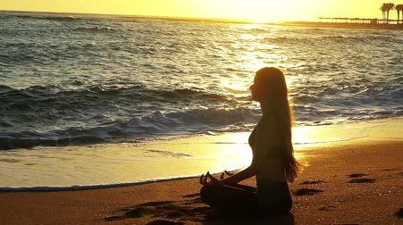 Yoga by sea and woman meditation in lotus position at the seaside with coming sea waves in sun light sunrise.