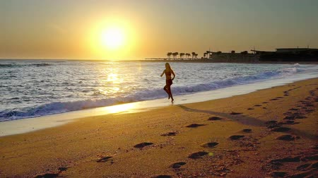 Jogging on beach with sea view and sunrise. Sport young woman run summer outdoor on sand.