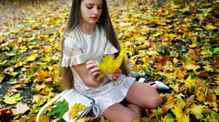 Safety for kids walking from school in autumn park alone. Carefree teen girl sitting on fall land and pick up bouquet of yellow leaves unaccompanied adults.