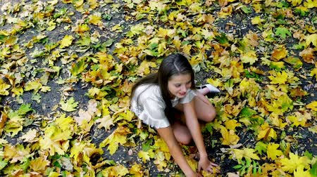 Slow motion autumn child girl in park sitting with leaves. Teenage girl learns to walk in heels and falls into fall foliage .
