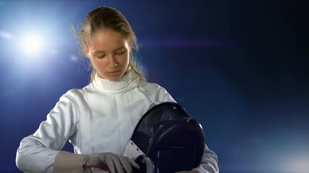 Sport girl fencer with epee before competition in fencing hall with light background. Athlete preparing for battle.