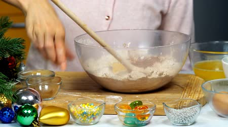 Christmas gingersnap with female hands. Xmas ingredients and decorations for ginger cookies. Woman kneading dough in deep bowl with wooden spoon Wideo