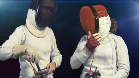Women fencers fight. Sport girl with epee puts on mask and becomes combat stance getting ready on competition in fencing hall with light dark background. Wideo