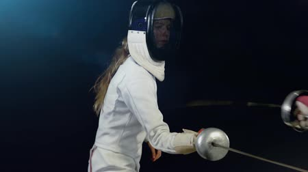 Women fencers fight. Sport girl fencer with epee on competition in fencing hall with light dark background.