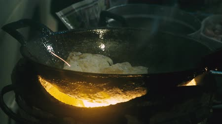 kluski : Close-up video of restaurant chef cooking stir noodle Bangkok street food with metal flipper and flying pan on Thai old vintage fire stove. Wideo