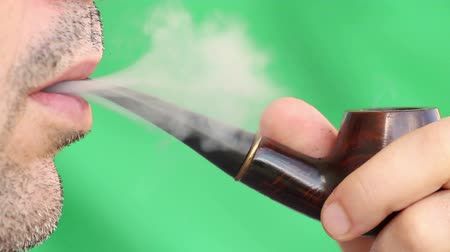 cygaro :  Caucasian man smoking cigar on green background, selective focus, isolated Wideo