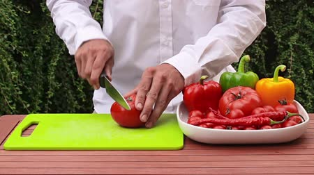 food preparation : young man cutting vegetables and tomatoe in the garden during hot sunny day Stock Footage