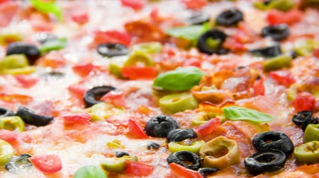 olive colored : Beautiful multi colored and crispy pizza with basil, melted cheese and salami slowly turning on rotating table Stock Footage