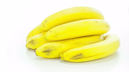 banany : Raw banana rotating on the white table with white seamless background Wideo
