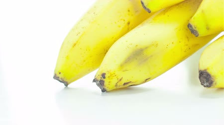 ve slupce : Raw banana rotating on the white table with white seamless background Dostupné videozáznamy