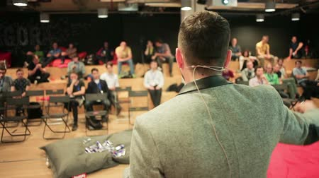 event : Caucasian speaker teaching at international conference, wide shot