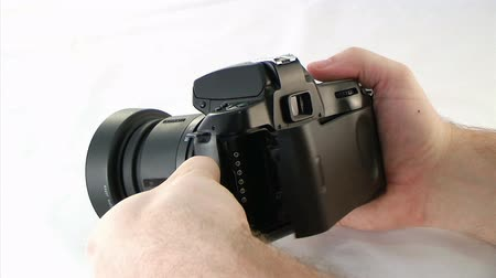 negatives : Person holding a SLR camera and loading it with film, set on a white background.  Stock Footage
