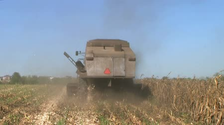 cabeçalho : Farmer operating machinery during harvest of cornfield, on midwest farm.