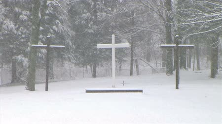 ruhanilik : Slow zoom of peaceful crosses across lake, during winter snowstorm.