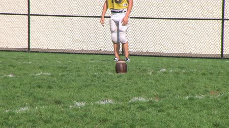 futbol : High school kicker practicing onside kick during training on practice field.