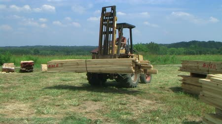 empilhamento : Worker using forklift to unload lumber at construction site, with external audio.