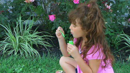 küçük kız : Cute little girl in pink dress sitting is grass blowing bubbles and laughing.
