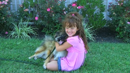 kobieta pies : Cute little girl hugging her dog and smiling while sitting in grass.