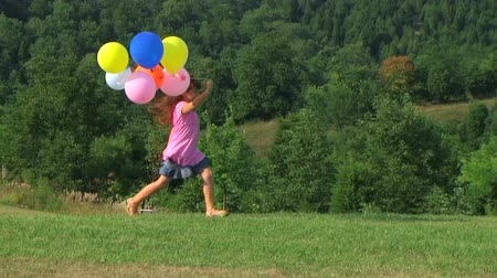 léggömb : Cute little girl having fun while skipping with balloons in country.