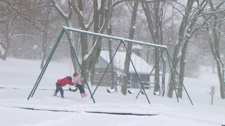 log cabin : Kids playing in late winter snowstorm as a boy pushes his sister on swing in park, with log cabin in background.