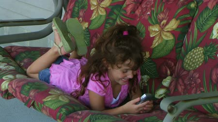 squirm : Cute little girl laying on porch swing while talking on cell phone.