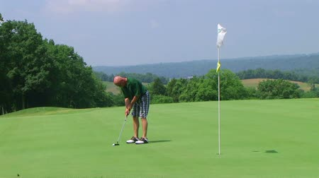 jogador : Golfer uses putter to sink long putt into hole with flagstick, on country club course. Vídeos