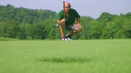 поле для гольфа : Close-up of golfer using putter to sink long putt into hole, rack focus with shotgun audio.