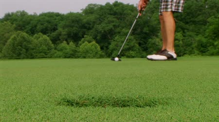 golfen : Close-up van golfer putter met lange putt zinken in gat op groen.