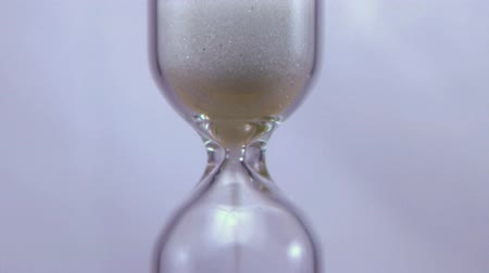 čas : Time lapse of hourglass with sands of time running out, a means of keeping time.