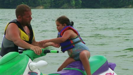 otec : Father helps his daughter get off jet ski by lifting her to safety.