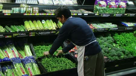 супермаркет : Worker inspecting produce display of fresh green beans in grocery store.