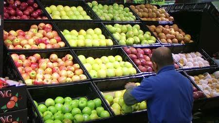 üretmek : Worker facing fresh produce display of green apples in grocery store. Stok Video