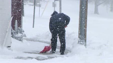 télen : Man shoveling snow to clear sidewalk during late winter blizzard.